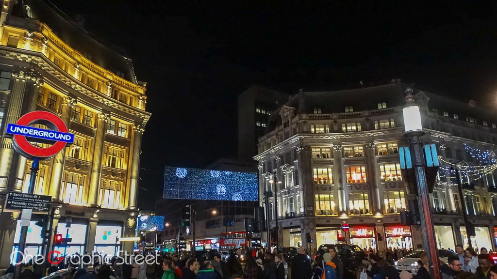 Photography on Oxford Street with the Christmas lights and the London underground sign.
